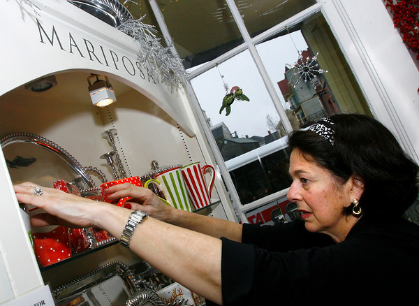 "Gloucester: Kathy Cuddyer, owner of Stone Leaf, arranges items in her shop, which she says has been doing well this holiday season. ""The business owners are doing everything they can to keep people on Main Street"" she says, ""We're open longer, wrapping gifts, and many are offering refreshments."" Photo by Kate Glass/Gloucester Daily Times Wednesday, December 17, 2008"