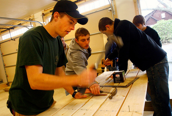 Rockport: Chris Fisher, left, helps construct one of five picnic tables he is creating for the town of Rockport as part of his Eagle Scout project. Fisher enlisted the help of several friends, including Trevor Smith, center, and Nick Favaloro, right, for the construction, which took place in the garage of Selectman Armand Aparo's home.<br /> Photo by Kate Glass/Gloucester Daily Times Sunday, December 28, 2008