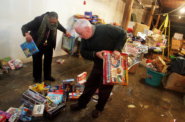 Gloucester: Tim Riley, Deputy Director of Action Inc, and Loretta Peres, coordinator of Project Uplift, pick up wet toys off the basement floor in the Action Inc. building on Pleasant Street Friday morning.  Water from heavy rains overnight caused a significant amount of water to leak into the basement damaging toys being stored for Toys for Tots. Mary Muckenhoupt/Gloucester Daily Times