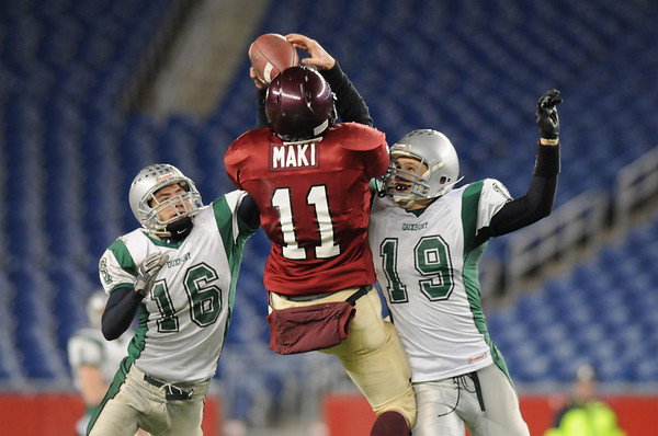 Gloucester's Dylan Maki goes up between Duxbury's Gilbert Brown (left) and Jared Wright at Gillette Stadium in Foxboro,Mass Saturday night December 6,2008.