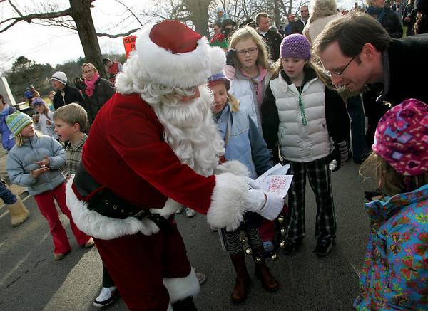 Manchester: Santa reads a wish list from Annabelle Rogers, 5, right, standing with her father, Josh, after santa arrived to Masconomo Park by firetruck Saturday afternoon.  One thing on Annabelle's list was a little red riding hood costume. Mary Muckenhoupt/Gloucester Daily Times