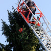 Manchester: Manchester Fire Captain Tod Bigger puts a large snowflake at the top of Manchester's Christmas tree Wednesday afternoon as an employee of R.P. Lations Tree Service works on the lights. The official lighting will take place on Sunday. Photo by Kate Glass/Gloucester Daily Times Wednesday, December 3, 2008