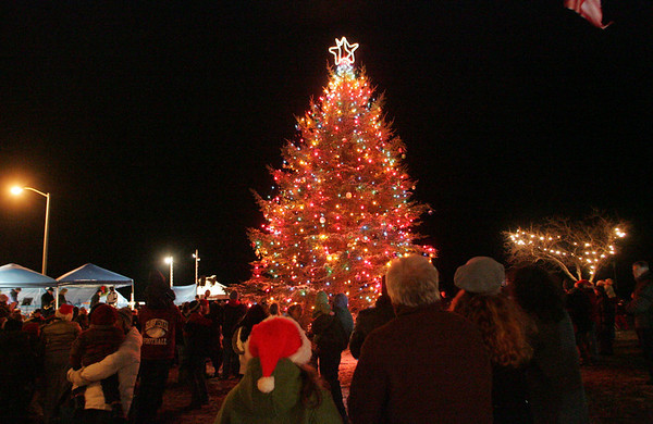 Gloucester:  People stand around the tree at Kent circle during the Gloucester tree lighting ceremony Sunday night. Mary Muckenhoupt/Gloucester Daily Times