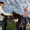 Essex:  Brook Soininen, 3, of Ipswich waits for her pony ride at the Essex Clam Fest at Memorial Park Saturday.  The Clam Fest offered a variety of children's activities and games as well as plenty of clam chowder to sample. Also pictured is Katie Spanos who lead the pony around the park. Mary Muckenhoupt/Gloucester Daily Times