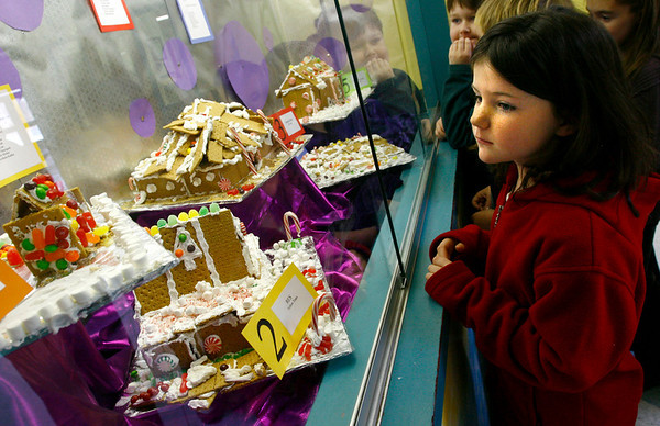 Rockport: Libby Ward, a third grader at Rockport Elementary School, looks at five gingerbread houses that students made during an after school program on Monday. Students and faculty pay a penny to vote on their favorite house and all the money will go toward their new playground, the Amelia Grace Place. Voting continues through December 23rd. Photo by Kate Glass/Gloucester Daily Times Tuesday, December 16, 2008