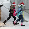 Gloucester: From left, Alexis McLean, 10, and Alexis Raymond 9, of Gloucester run accross Hancock Street as the snow begins to pile up Friday afternoon.  The girls didn't seem to mind the snow as they dashed from store to store doing Christmas shopping.  Mary Muckenhoupt/Gloucester Daily Times