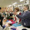 Gloucester:  Barbara DeCoste, right, standing with Robin Davis, holds a mirror up so that Pavla Divisova can see the hat she tried on at the Holiday Fair at St Ann Church Saturday afternoon. Mary Muckenhoupt/Gloucester Daily Times.