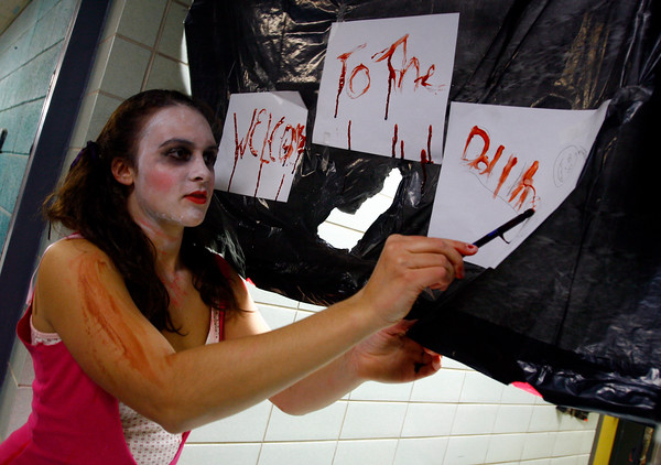 """Manchester: Elsa Keefe uses fake blood to write """"Welcome to the Dollhouse"""" outside one of the rooms at Manchester Essex's """"Haunted Hallways"""" on Wednesday. This year was the last year for the event since students are expected to be in the new building next year. Photo by Kate Glass/Gloucester Daily Times Wednesday, October 29, 2008"""