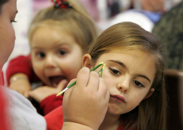 Gloucester:  Matina Billante, 5, of Gloucester gets a Christmas tree painted on her cheek by Keana Salvi-Souza while her little sister Daunika, 3, makes a silly face at the Holiday Fair at St. Ann Church Saturday. Mary Muckenhoupt/Gloucester Daily Times