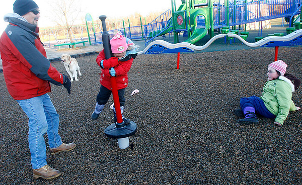 Rockport: Randy Burley of Rockport watches as his daughters, Mariah, 5, and Cara, 9, take turns spinning at the Amelia Grace Place behind Rockport Elementary School on Tuesday afternoon. Photo by Kate Glass/Gloucester Daily Times Tuesday, December 30, 2008