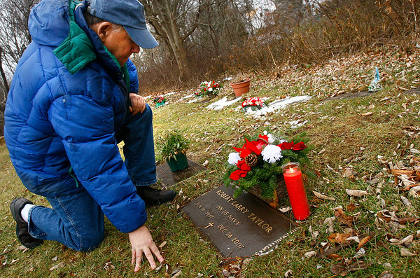 Gloucester: Jim Dinsmore kneels at the grave of close friend Robert Taylor, who died in the Lorraine fire last year. Dinsmore placed flowers and a candle on the grave as a memorial wearing the hat he had planned on giving Taylor for Christmas last year. Photo by Kate Glass/Gloucester Daily Times Tuesday, December 9, 2008