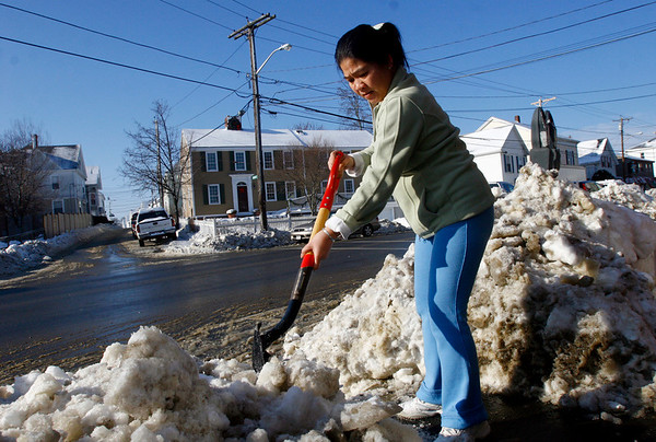 Gloucester: Kathy Wang chips away at the ice on the sidewalk in front of Perfect Nails on Washington Street after this weekend's storms. Photo by Kate Glass/Gloucester Daily Times Monday, December 22, 2008