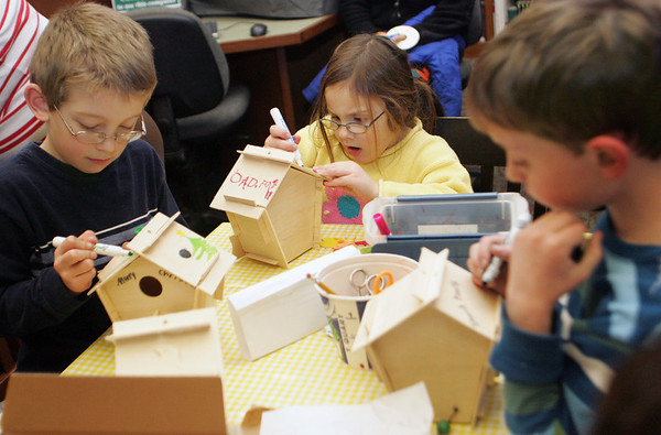 Manchester: From left, Will Russo, 7, Faith Costello, 5, and Sam Dellicker, 9, work on decorating the birdhouses that they put together at The Manchester Public Librbary's winter crafts hourThursday afternoon.  Children could make a variety of homemade crafts to give as gifts with wrapping paper provided. Mary Muckenhoupt/Gloucester Daily Times