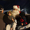 Gloucester: James Sanfilippo picks up his som Sam, 11 months, off of Santa's lap while his other son James, 2, tells Santa his Christmas list at the Christmas tree lighting ceremony at Kent Circle Sunday night. Mary Muckenhoupt/Gloucester Daily Times