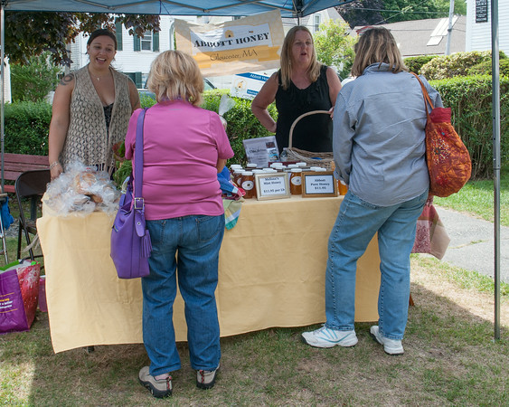 DESI SMITH/Staff photo.    Carson afKlintaberg (left) of afKlintaberg Bakery in Lanesville talks to a shopper about her Nisu, a type of Finnish bread they bake which is very popular, as Melissa Abbott of Abbot Honey in Gloucester talks about her honey, as the share a booth at the Rockports Farmers Market  Saturday morning corner of Broadway and Mt. Pleasant Street. August 16,2014
