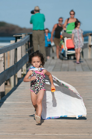 """DESI SMITH/Staff photo.   """"Super Day""""  Lola Thompson 4, visitng from NY City, looks like she means business, as she races a head of her family (in background) wearing her beach towel as a cape, as they leave Good Harbor Beach Thursday afternoon.   August 28,2014"""