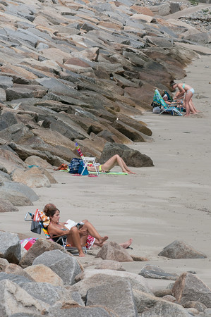 DESI SMITH/Staff photo.   Beach goers settle in to their spots along some rocks on Back Beach in Rockport on a recent afternoon August 16,2014