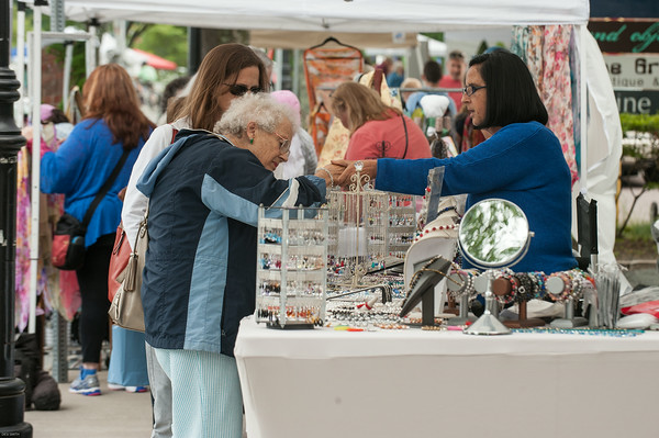 DESI SMITH/Staff photo.    Marie Helen Carver of Ipswich, trys on a bracelet from Karol Peralta of Karol Peralta Jewelry as Marie's daughter Christine Lawton visiting from Calafornia looks on at Manchester's celebration of the arts Saturday afternoon on Beach St.    August 2,2014
