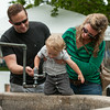 DESI SMITH/Staff photo.   Matt and Allie Desmeules of Hamilton, helps their son James 1 1/2 get a drink of water at the water fountain near the police station,while out walking around at Manchester's celebration of the arts Saturday afternoon at the Public Library.    August 2,2014
