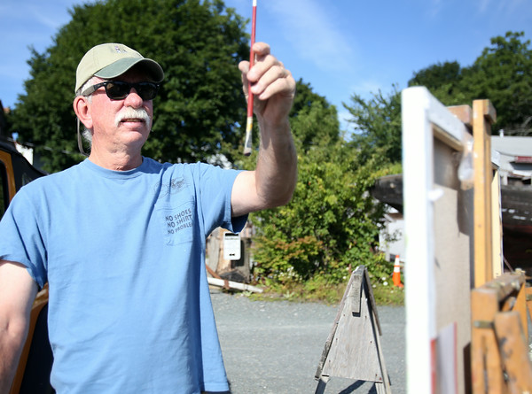 Salem native John Pydynkowski, uses his paint brush as a measuring tool as he starts to paint Burnham's Boat Yard on Saturday morning. Local artists painted scenes of Essex on Saturday and the paintings will be auctioned off on Sunday during the 3rd Annual En Plein Air Painting and Wet Paint Auction, sponsored by the Essex Merchants Group. DAVID LE/Staff  photo. 8/16/14.