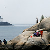 PAUL BILODEAU/Staff photo. People take to the rocks at Stage Fort Park with the Easter Point jetty in the background.
