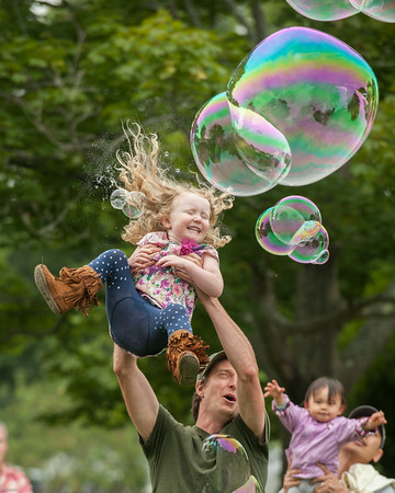 DESI SMITH/Staff photo.    Andy Luman of Gloucester, holds his daughter Hazel 4, up as a bubble bursts in her face, while attending Manchester's celebration of the arts Saturday afternoon at Masconomo Park.    August 2,2014