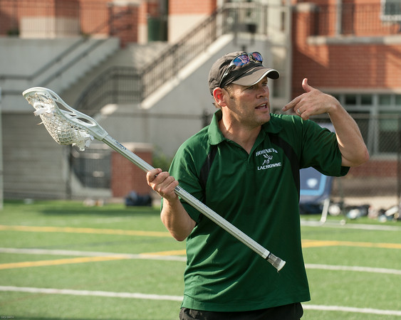 DESI SMITH/Staff photo.  Manchester Essex head varsity coach John McCavanagh, runs some young lacross players through some lacross drills at a Lacross camp held Wednesday afternoon at Hyland Field, at Manchester Essex Regional High School.   August 6,2014
