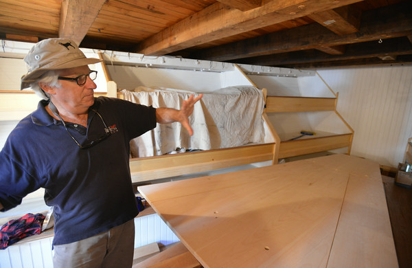 RYAN HUTTON/ Staff photo.<br /> John Fuller, executive director of Schooner Adventure, shows off the restored crew quarters and galley table in the hold of the ship.