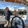 RYAN HUTTON/ Staff photo.<br /> John Fuller, executive director of Schooner Adventure, talks about the restorations the ship has undergone wile leaning on the ship's wheel.