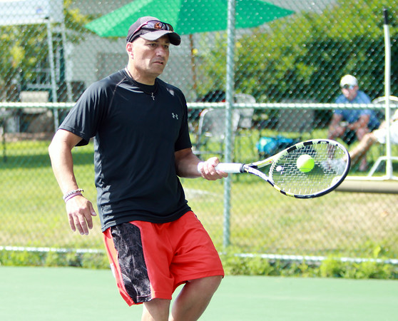 David Salah keeps his eyes on the ball while returning a serve during the Bass Rocks Men's Member/Guest Tournament A-Flight players match on Saturday morning. DAVID LE/Staff  photo. 8/16/14.