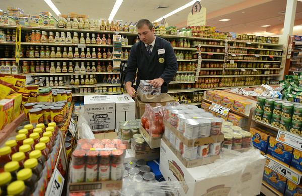 RYAN HUTTON/ Staff photo.<br /> Five-year employee Adam Lovasco unpacks a pallet of cocktail sauce in the Gloucester sMarket Basket on Wednesday.
