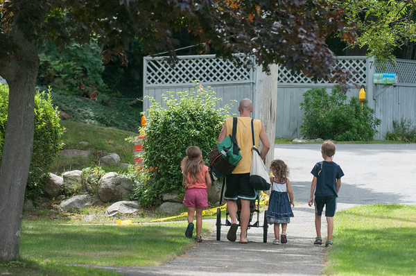 DESI SMITH/Staff photo.   A father and his children head out for a stroll just of Pooles Lane in Rockport on a recent sunny afternoon.   August 16,2014