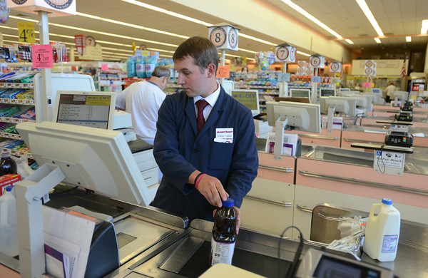 RYAN HUTTON/ Staff photo.<br /> Torrey Allen, 24, a four year veteran of the store, is one of the only cashiers on duty as the customer boycott of Market Basket continues.