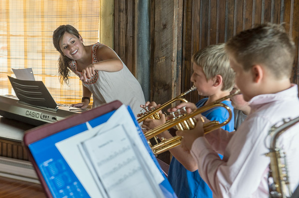 DESI SMITH/Staff photo.   Alexa Tarentino, who is a graduate of the Eastman School of Music, directs Daniel Merz and Levin Boettcher as they play their trumpets in a small jazz concert held at the Old Firehouse Trust on Mount Pleasant Street friday afternoon.      August 15,2014