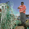 Gloucester: Sam Novello, a retired fisherman, repairs fishing nets for a friend at the Gloucester Marine Railway on Rocky Neck Friday afternoon.  Novello says that nets are getting ripped because fishing boats are fishing in new areas. Mary Muckenhoupt/Gloucester Daily Times