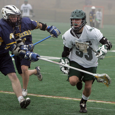 Manchester: Manchester Essex's Drew Gosnell runs up field trying to protect the ball from Lynnfield defenseman George Hennessy during the lacrosse game at Coach Ed Field Field Friday afternoon. Mary Muckenhoupt/Gloucester Daily Times