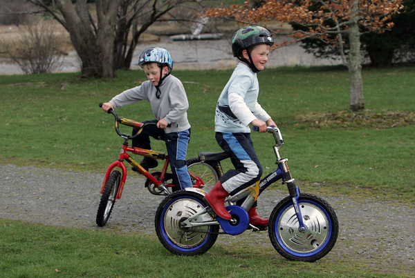 Manchester: Connor Cunningham, 5, left, and his twin brother Aidan ride their bikes at Masconomo Park in Manchester Park Thursday afternoon.  The boys enjoyed riding around tghe baseball diamond and riding through big puddles in the grass leaving mud splashes on the back of their shirts. Mary Muckenhoupt/Gloucester Daily Times