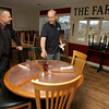 Essex: Noah Goldstein, left, talks with his cousin, Brad Atkinson, as he sets a table at their new restaurant, The Farm Bar & Grille on Western Ave in Essex, which is opening today. Photo by Kate Glass/Gloucester Daily Times Tuesday, April 14, 2009