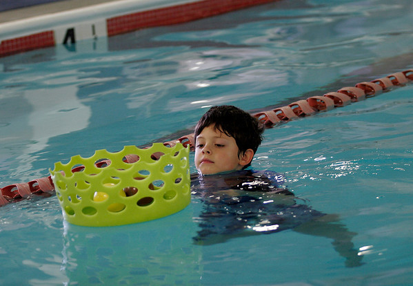 Manchester: Xander Everitt, 5, of Gloucester collects pool toys during family swim time at the Manchester Athletic Club. Photo by Kate Glass/Gloucester Daily TImes
