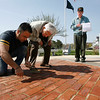 Gloucester: Salvatore Bologna, left, finishes the first section of bricks inscribed with names of Gloucester veterans at the World War II Memorial at Kent Circle on Monday morning as Mike Linquata, center, and Mel Olson, right, both members of the World War II Memorial Committee, check their list of names. One third of the next section has already been sold and the committee anticipates finishing that section by the end of this summer. Photo by Kate Glass/Gloucester Daily Times Monday, April 27, 2009
