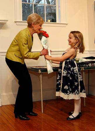 Manchester: Rowan Schanley, 6, proudly hands her grandmother, Carole Schanley, a bouquet of flowers for being named Mancheseter's outstanding volunteer of the year during a ceremony at the Manchester Historical Society Monday night. Lisa Press, not shown, was named outstanding employee of the year. Photo by Kate Glass/Gloucester Daily Times Monday, April 13, 2009