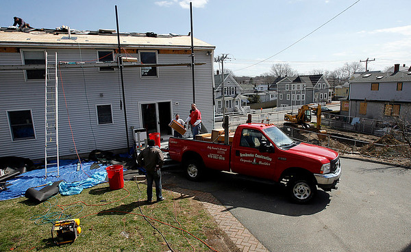 Gloucester: Darren Collins, owner of Breakwater Construction, directs his crew as they work on 78 Eastern Ave, which was damaged when the house next door exploded in January. The house will get a new siding, a roof, and decks along with other cosmetic repairs. Photo by Kate Glass/Gloucester Daily Times Thursday, April 9, 2009