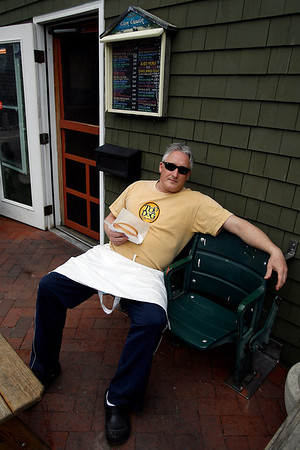 Rockport: Scott Lucas, owner of Top Dog on Bearskin Neck, relaxes in two seats from Fenway Park that were given to him as a belated wedding present. He has decided to put the seats at his restaurant instead of his home so more people can enjoy them. Photo by Kate Glass/Gloucester Daily Times Wednesday, April 1, 2009