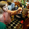 "Manchester: Bella Wright, 3, takes a pot with yardlong bean seeds during a Family Edible Gardens program at the Manchester Public Library yesterday afternoon. Barbara Emerson of ""Have Green Thumb"" showed the children how to nurture a seed into a plant. Photo by Kate Glass/Gloucester Daily Times Tuesday, April 7, 2009"
