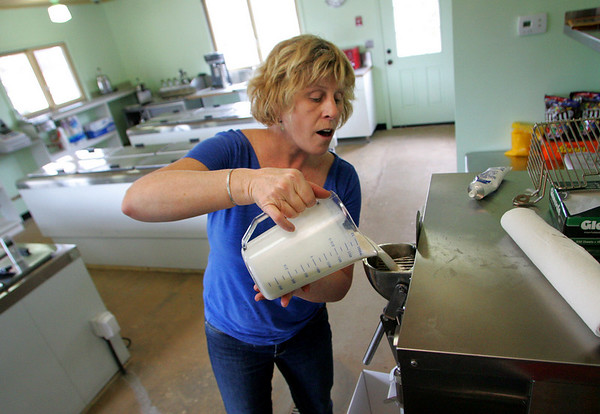 """Essex: Amy Ahearn pours all natural mix into an ice cream maker to make a batch of coffee ice cream at Down River Ice Cream, a """"green"""" business she is opening with her husband Joe.  The ice cream maker, or batch freezer, is air cooled and doesn't use water. Mary Muckenhoupt/Gloucester Daily Times"""