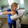 "Essex: Amy Ahearn pours all natural mix into an ice cream maker to make a batch of coffee ice cream at Down River Ice Cream, a ""green"" business she is opening with her husband Joe.  The ice cream maker, or batch freezer, is air cooled and doesn't use water. Mary Muckenhoupt/Gloucester Daily Times"