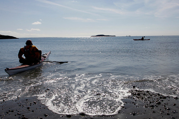 Manchester: Ross Bartosik of Amesbury, left, launches his kayak from White Beach, which is one of three locations being considered for kayak racks. The other two are Tuck's Point and behind Town Hall. Kate Glass/File Photo