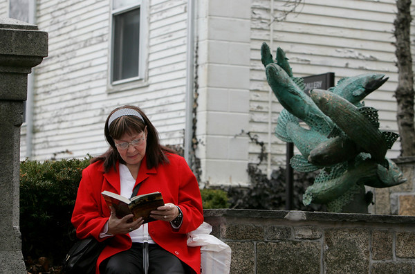 Gloucester: Donna Jeanne Pocknett of Gloucester reads a book while waiting for her ride in front of the Sawyer Free Library Thursday afternoon.  Mary Muckenhoupt/Gloucester Daily Times
