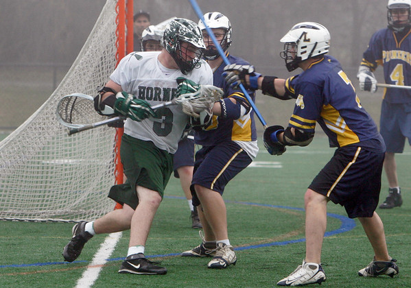 Manchester: Manchester Essex's Jack Bishop looks to escape from Lynnfield defenders during the lacrosse game at Coach Ed Field Field Friday afternoon. Mary Muckenhoupt/Gloucester Daily Times