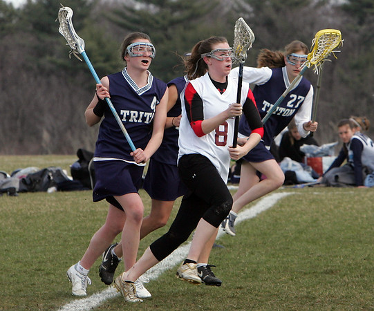 Gloucester: Gloucester's Jennavie Orrell carries the ball down the field  with Titon players, including Sara Nardone, left, in close pursuit during the girls lacrosse game at Magnolia Woods Friday afternoon. Mary Muckenhoupt/Gloucester Daily Times